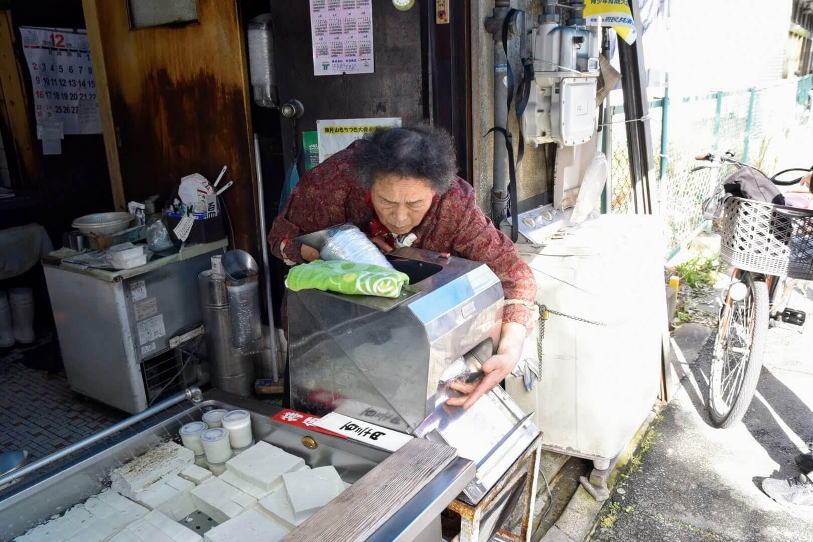 専用の機械に豆腐を流し込むおばあちゃん
