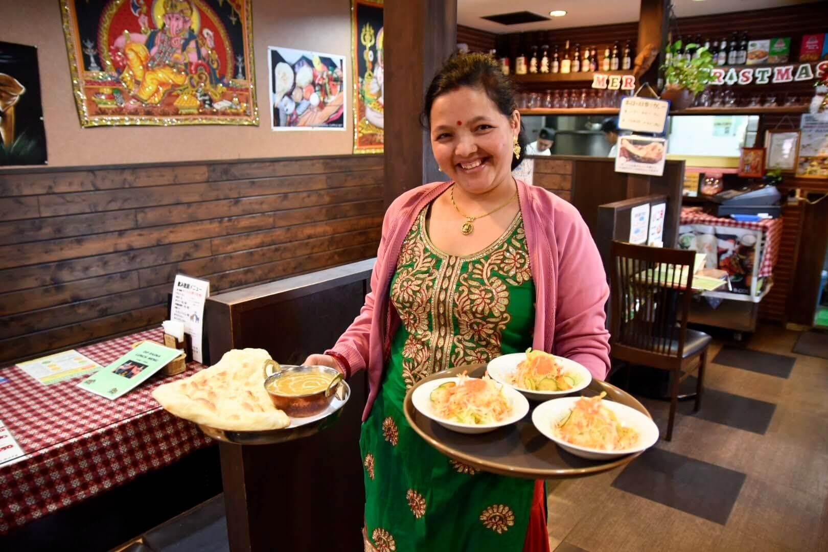 ディップ ラスナ 吹田店の素敵な奥さんが料理を運んでいるところ