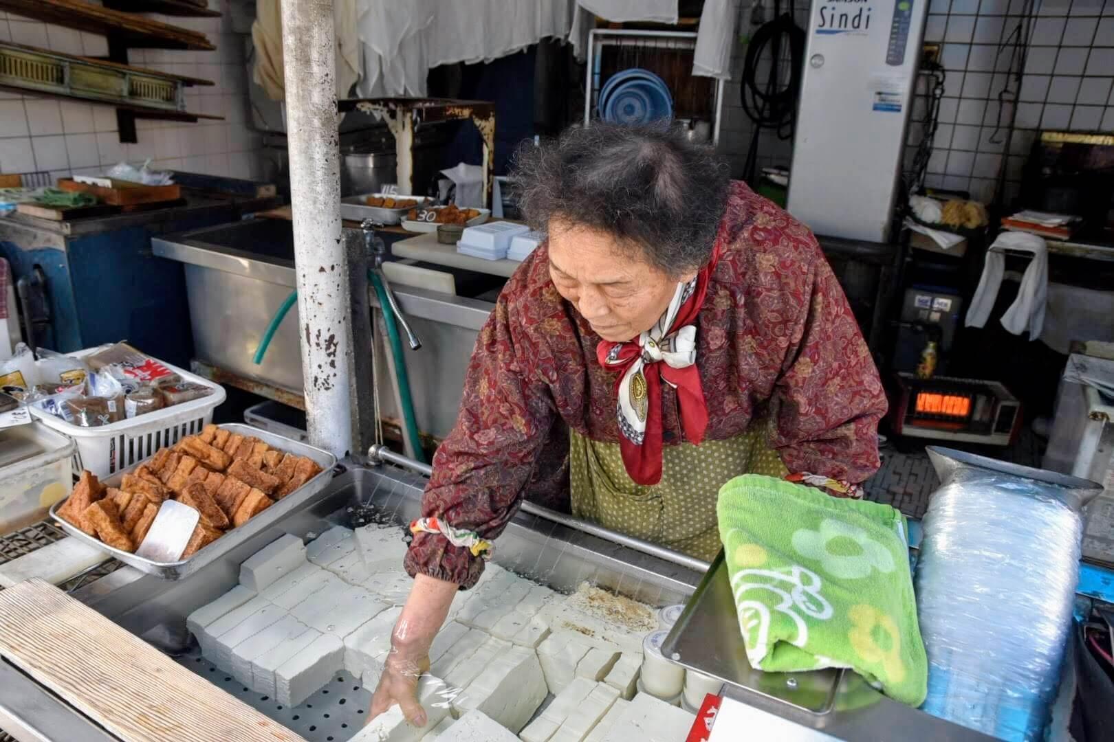 豆腐を取り出す『のとや』のおばあちゃん