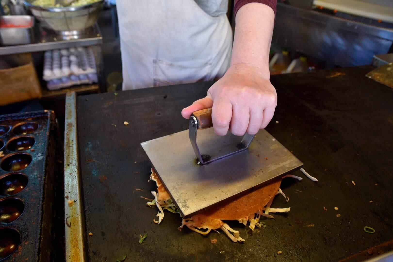 マルタ焼を鉄板に押さえつける動作