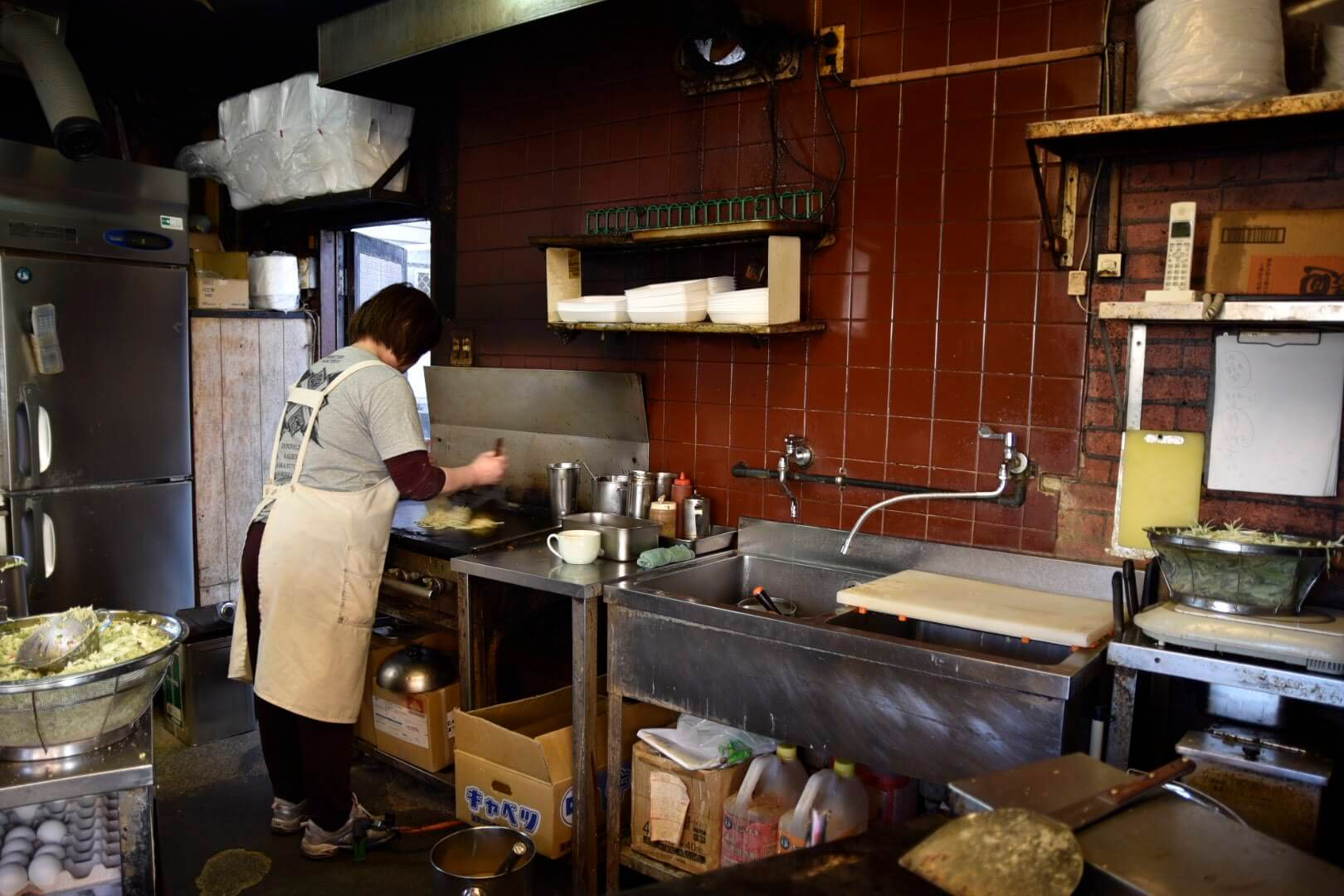 厨房の奥でマルタ焼を作る奥さん