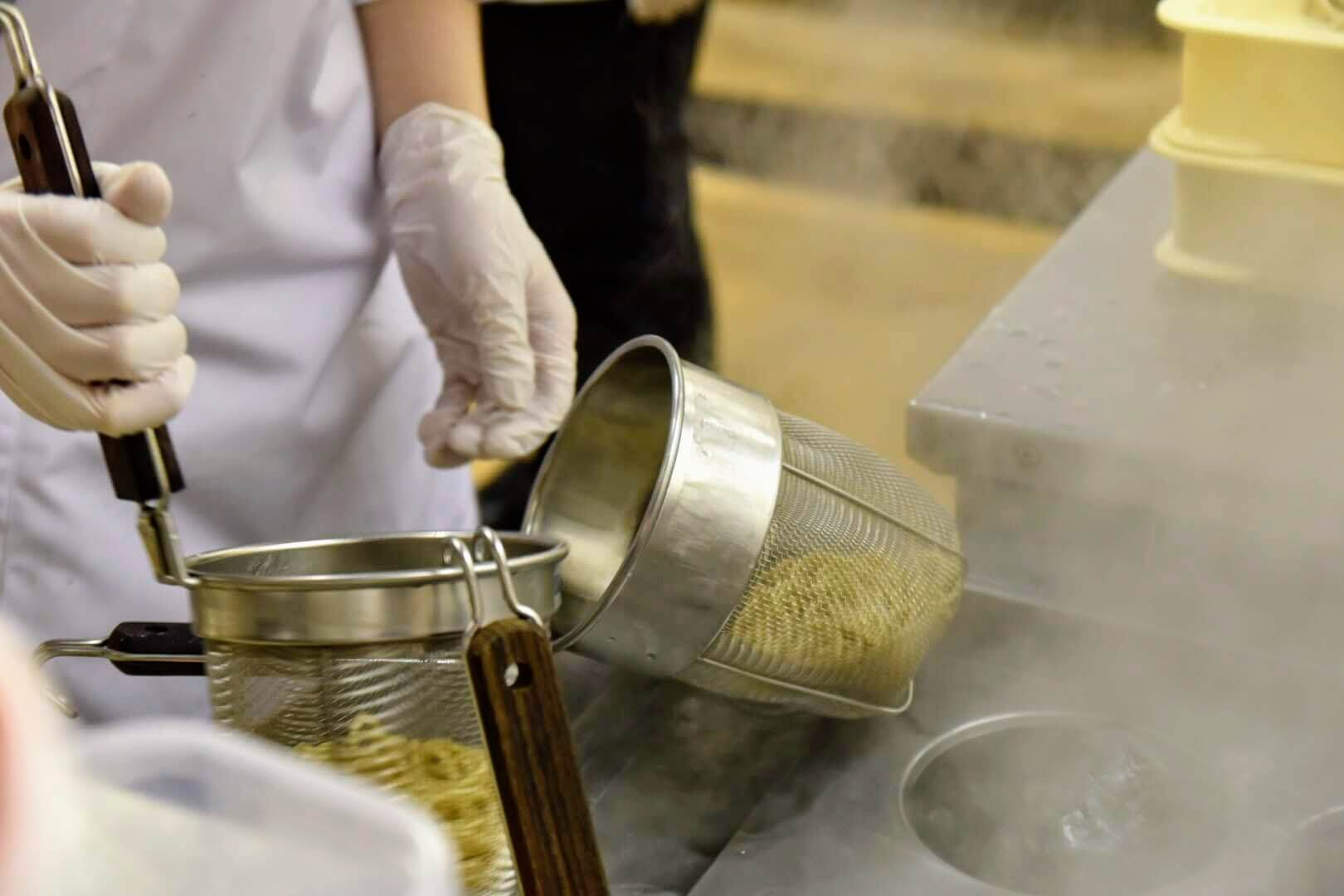 麺の茹で切りをするシーン