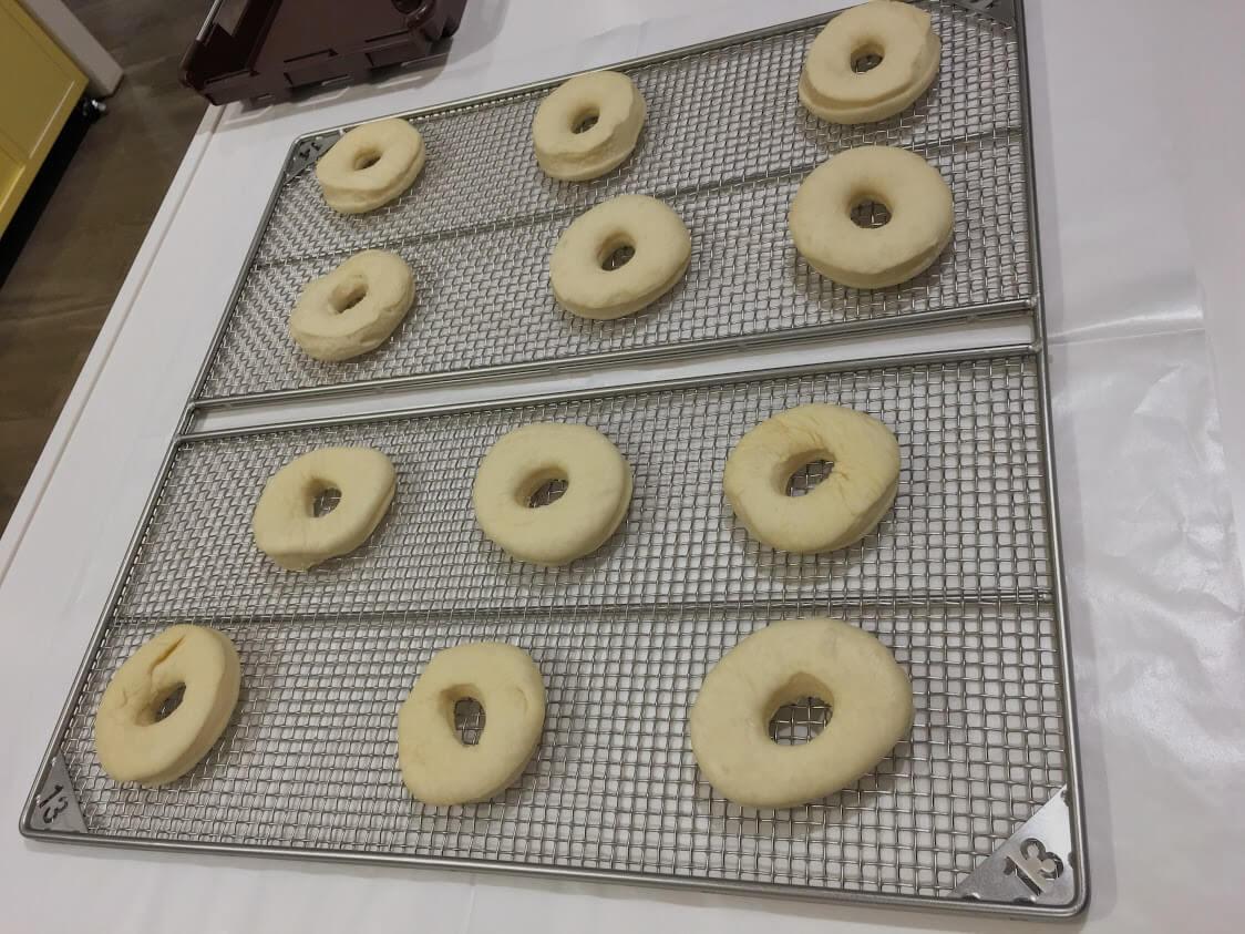 網のトレーに型抜きしたドーナツを並べる